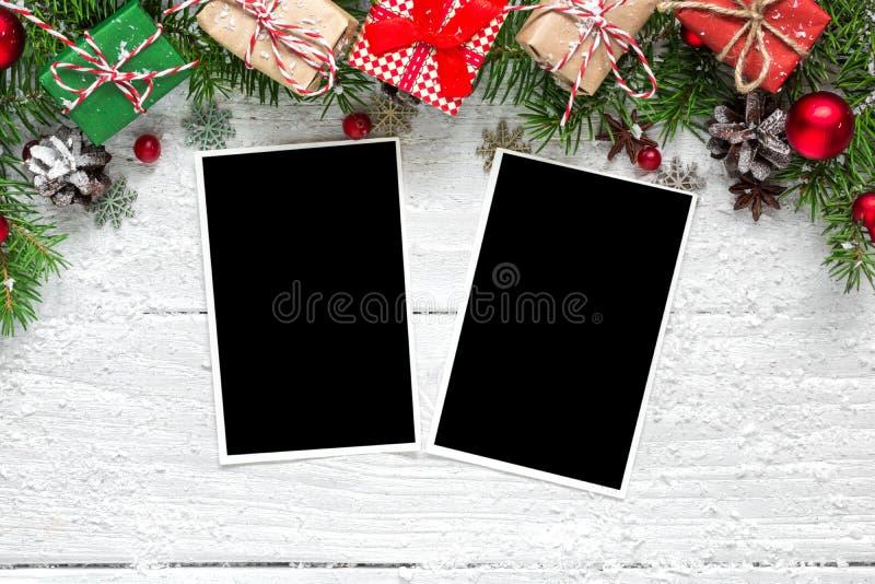 与杉树的圣诞节空白的照片框架分支,装饰和礼物盒在白色木背景 免版税库存照片