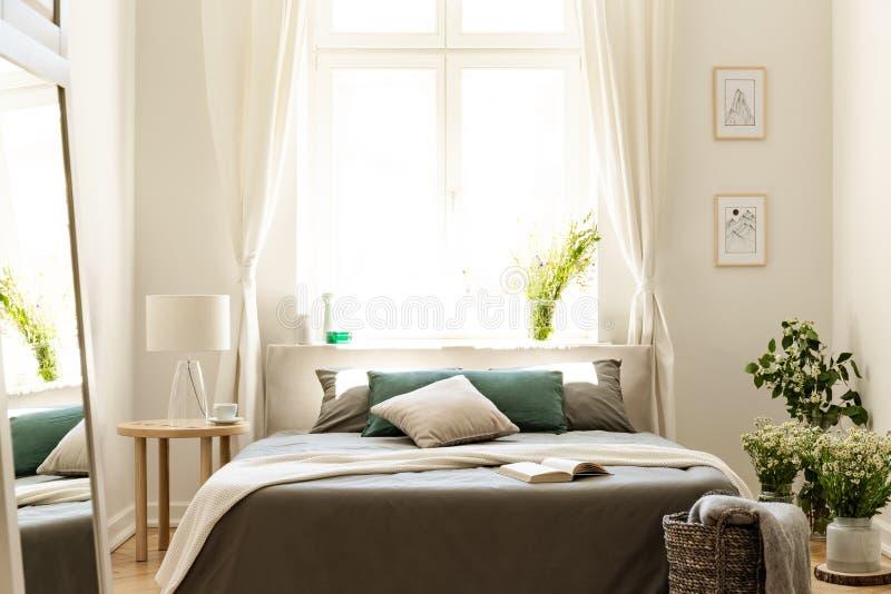 与束围拢的床的自然卧室内部野花 大晴朗的窗口在背景中 实际照片 库存照片