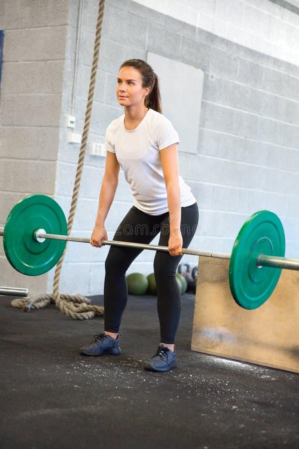 与杠铃的女运动员举重在健身俱乐部 免版税库存图片