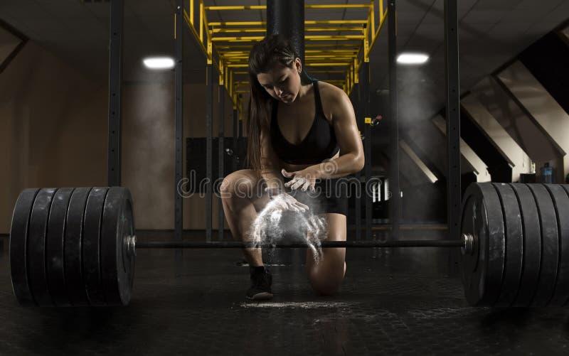 与杠铃的妇女锻炼在健身房 免版税库存照片