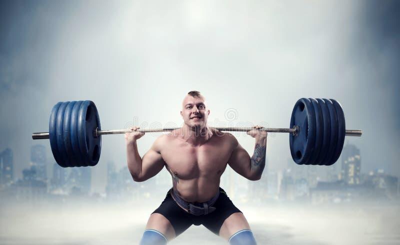 与杠铃的肌肉男性举重运动员锻炼 库存图片