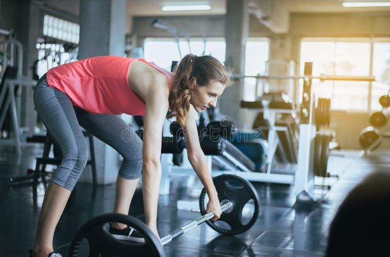与杠铃,女性的运动的妇女锻炼做行使在健身房 免版税库存图片