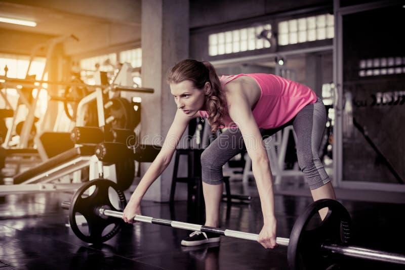 与杠铃,女性的运动的白种人妇女锻炼做行使在健身房 免版税图库摄影