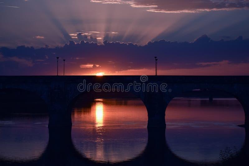 与来通过云彩和五颜六色的天空的光的惊人日落 在前景一个城市的桥梁后照光的 免版税库存图片