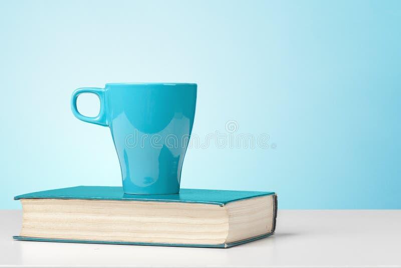 与杯子的书 图库摄影