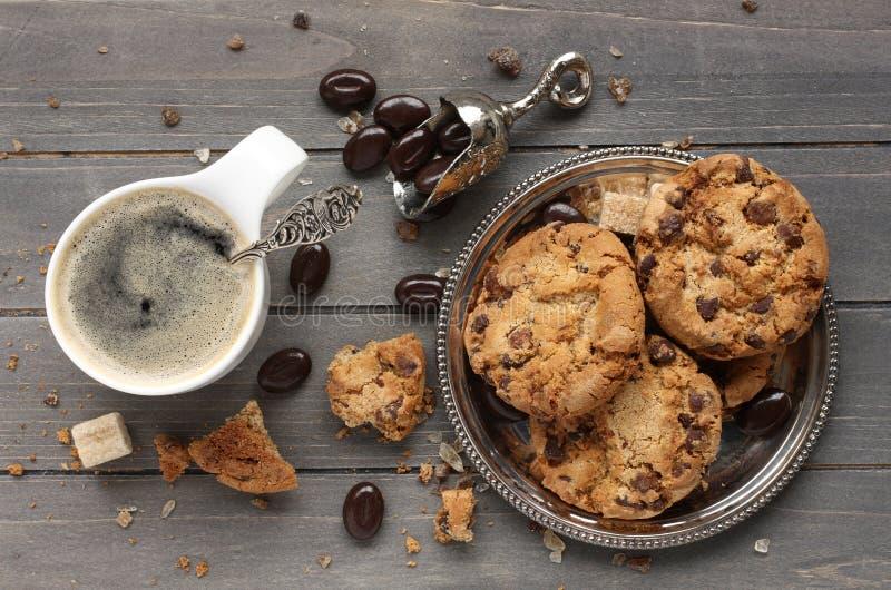 与杯子的新鲜的自创巧克力曲奇饼在老木背景的浓咖啡 库存照片