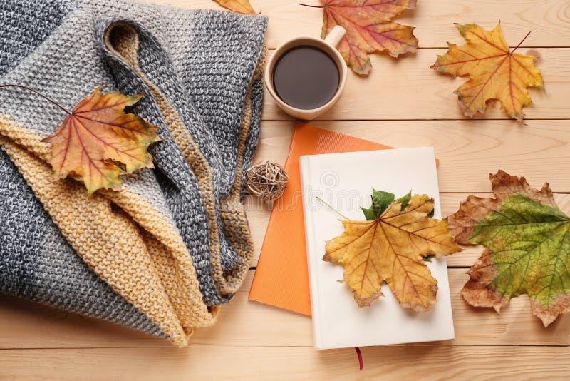 与杯子的构成可口加香料的热葡萄酒、温暖的格子花呢披肩、书和秋叶在木背景 免版税库存照片