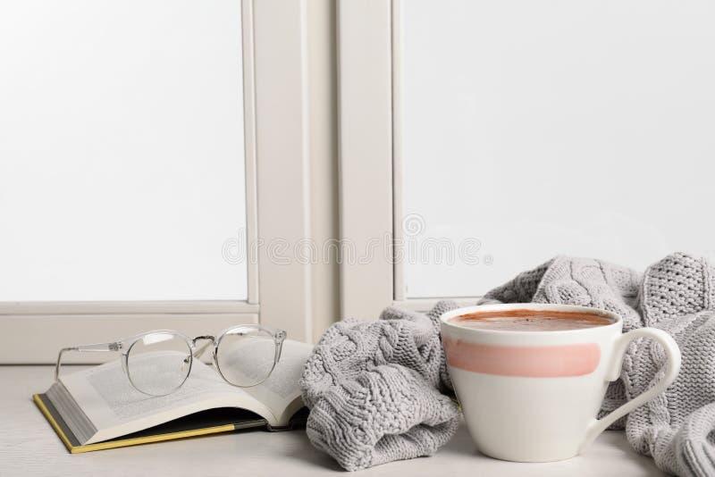 与杯子的构成巧克力热饮和书在窗台,空间文本的 免版税库存照片