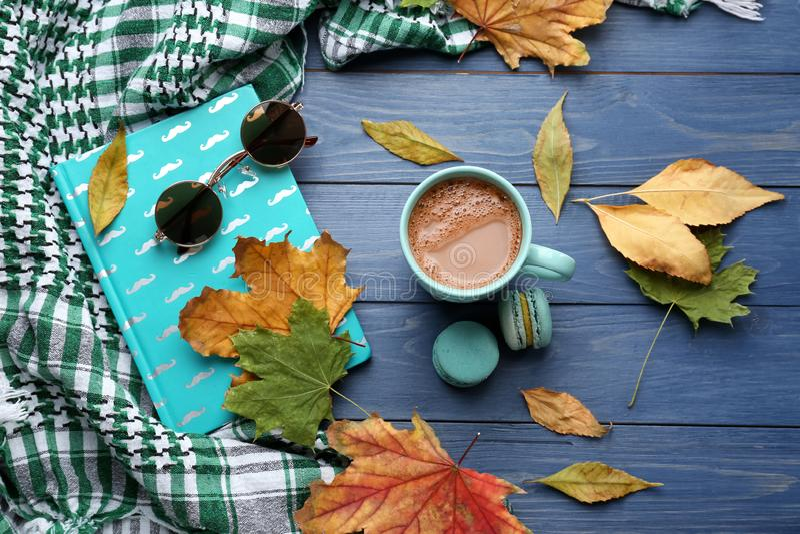 与杯子的构成芳香咖啡、温暖的格子花呢披肩、书和秋叶在颜色木背景 免版税库存图片