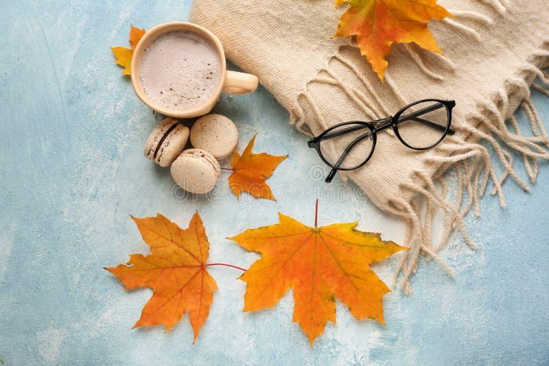 与杯子的构成芳香咖啡,温暖的格子花呢披肩和秋叶在颜色背景 图库摄影