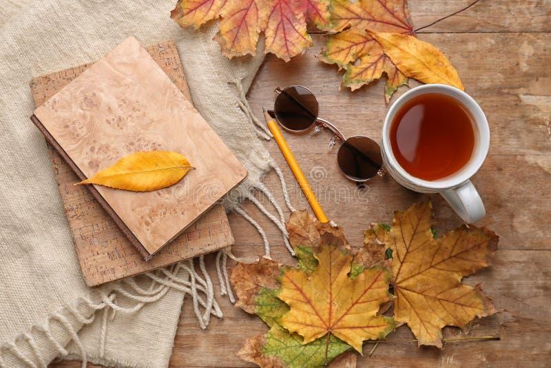 与杯子的构成芳香茶、温暖的格子花呢披肩、书和秋叶在木背景 图库摄影