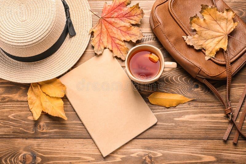 与杯子的构成芳香茶,帽子和秋叶在木背景 库存图片