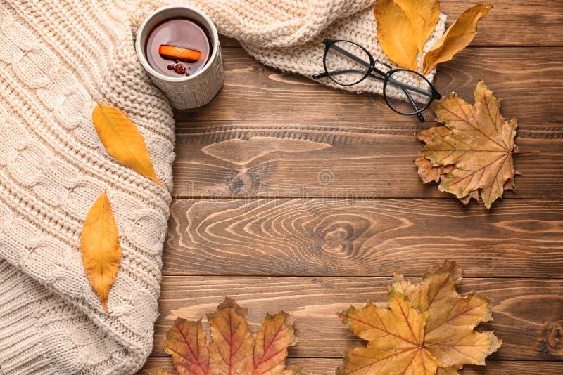 与杯子的构成芳香茶,温暖的格子花呢披肩和秋叶在木背景 免版税库存图片