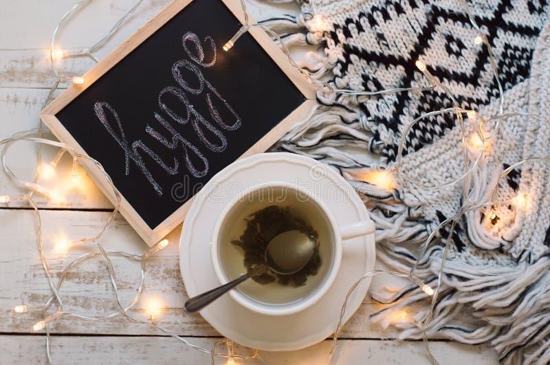 与杯子绿茶,黑板有白垩文字` hygge `的,黄灯和羊毛毯子的平的位置在木backgroun 库存图片