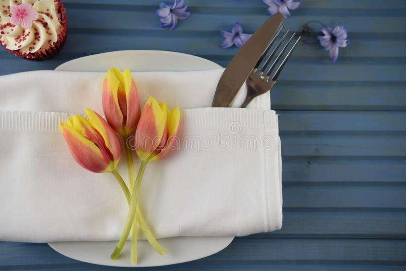 与杯形蛋糕和春天郁金香装饰的五颜六色的桌餐位餐具 免版税库存照片