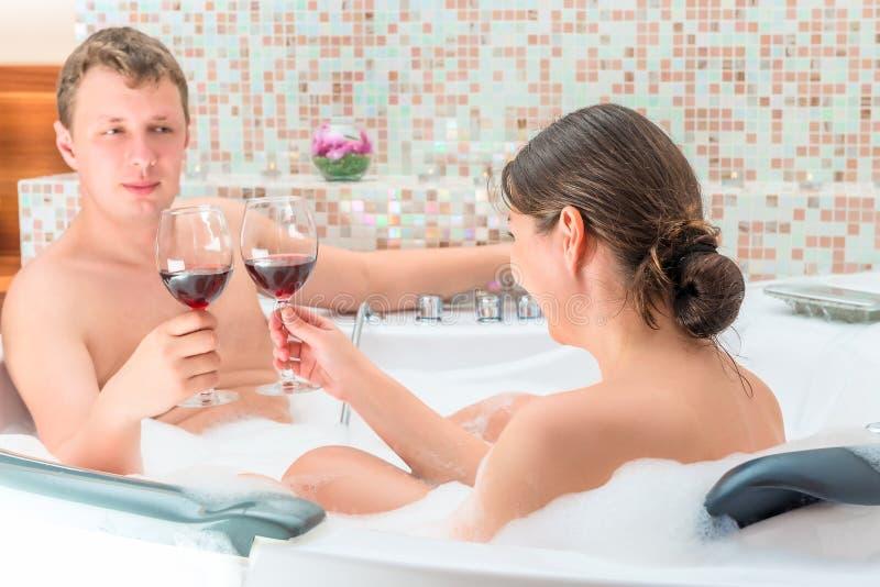 与杯的已婚夫妇在极可意浴缸的酒 库存照片