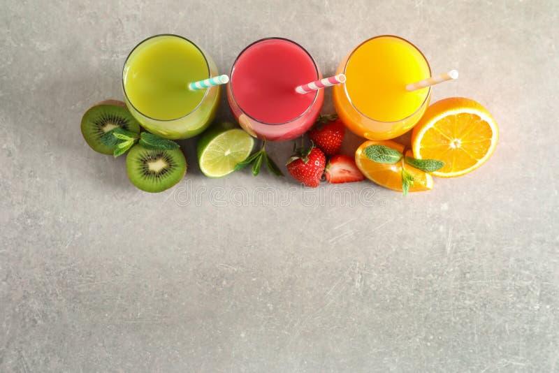 与杯的平的被放置的构成不同的汁液和新鲜水果在轻的背景 免版税库存图片
