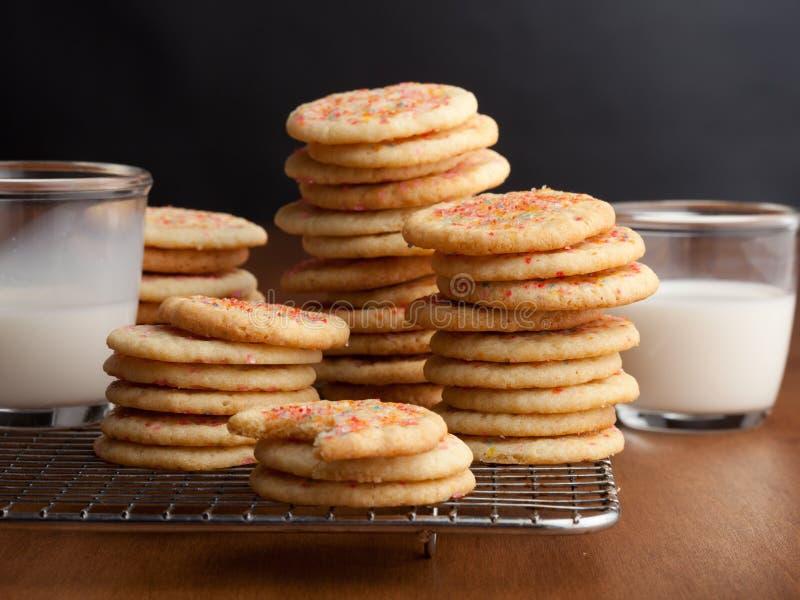 与杯的耐嚼的糖屑曲奇饼在桌上的牛奶 免版税库存照片