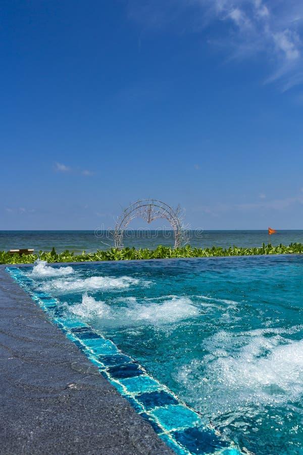 与极可意浴缸的无限水池在海滩胜地 库存照片