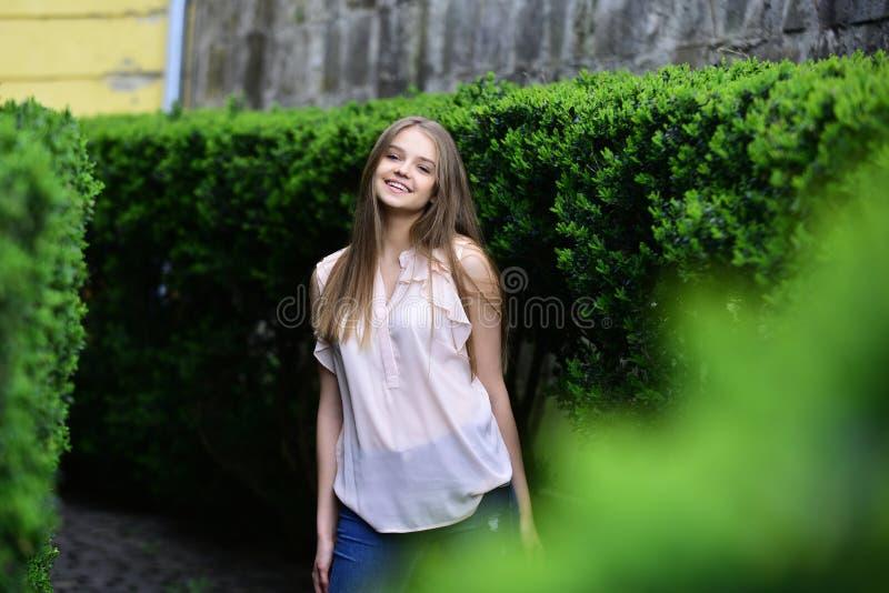 与构成的肉欲的模型在美发师以后 看女孩在绿色植物附近 室外的便衣的女孩 夏天或 免版税库存图片