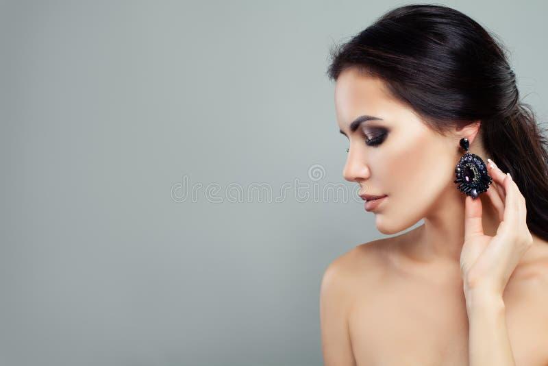 与构成的迷人的妇女时装模特儿和有黑宝石画象的首饰耳环 免版税库存照片