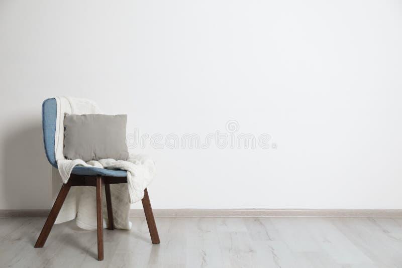 与枕头和格子花呢披肩的时髦的椅子 r 免版税库存照片