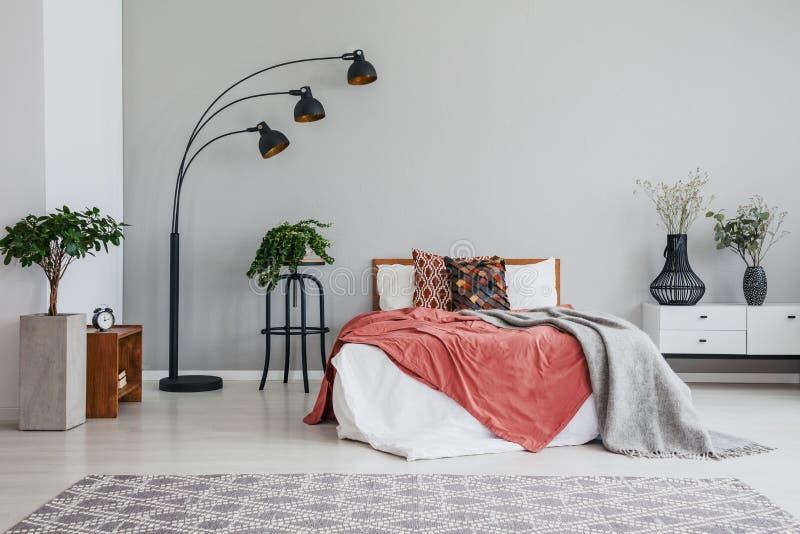 与枕头和毯子和白色床头柜的时髦的黑灯绿色植物床在现代卧室 免版税库存图片