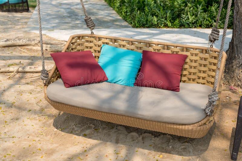 与枕头的垂悬的椅子在海滩 库存照片