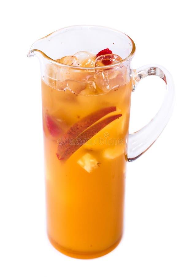 与果子片的橙汁过去在被隔绝的白色背景的一个水罐 免版税库存照片