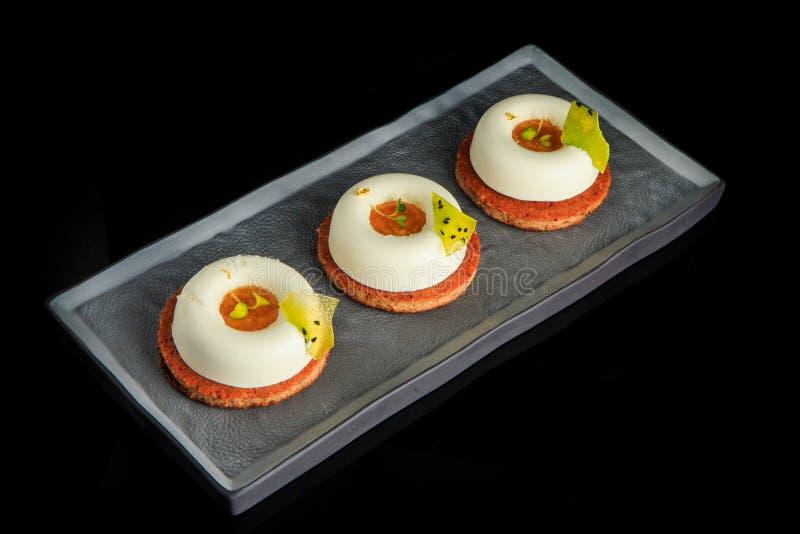 与果酱装填的特写镜头三微型白色奶油甜点蛋糕 免版税库存照片
