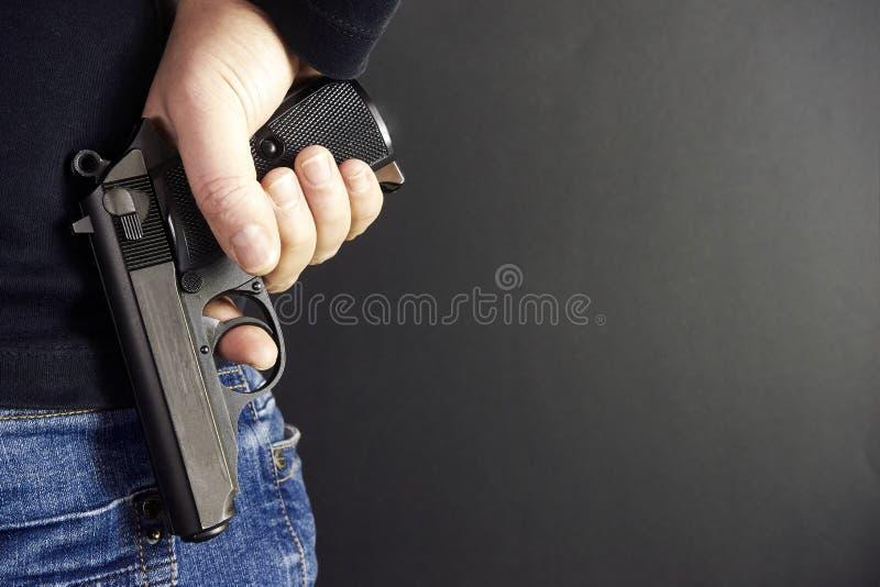 与枪关闭的凶手在与拷贝空间的难看的东西背景 库存图片
