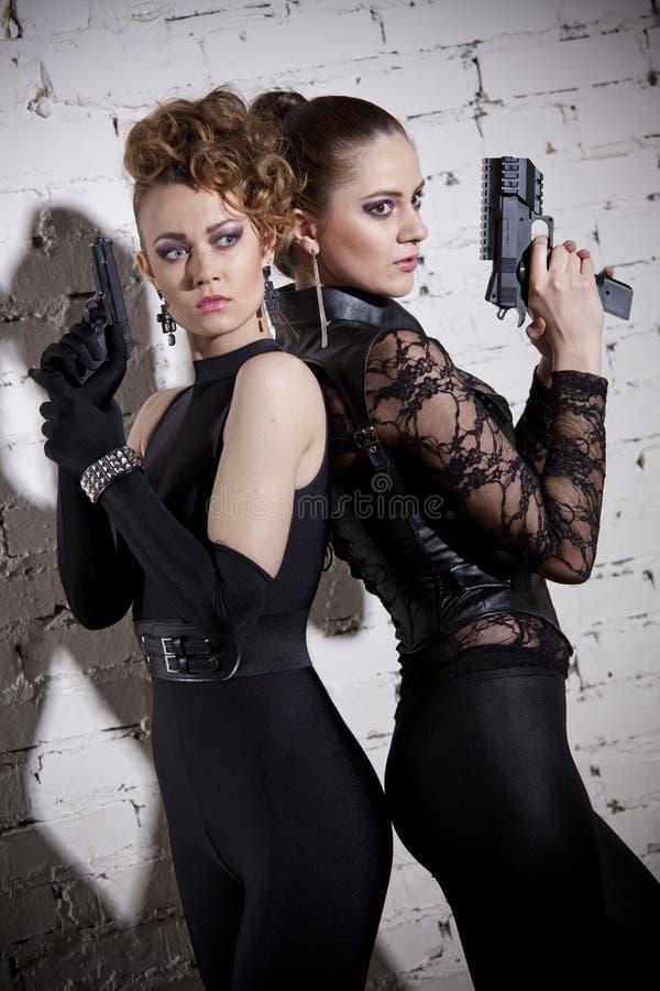 与枪的两个女性代理 图库摄影