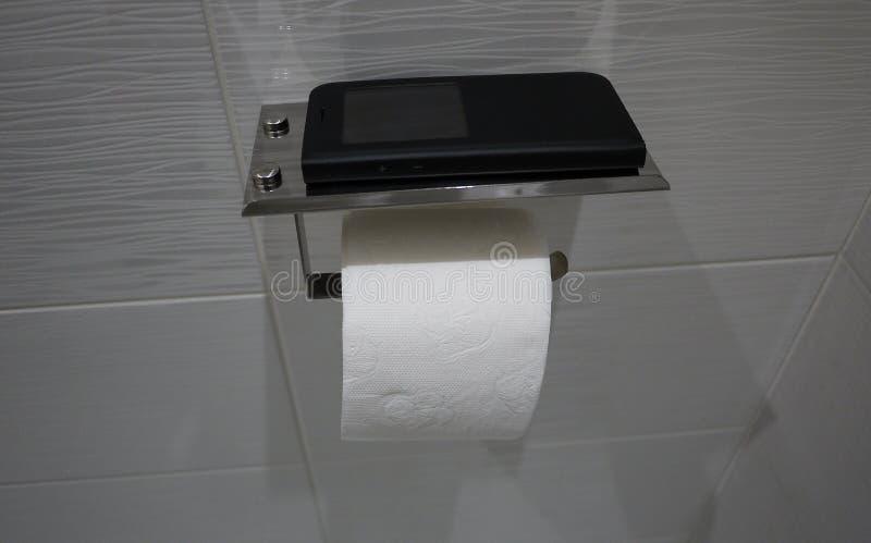 与架子的手纸持有人在洗手间,内部细节的智能手机的 图库摄影