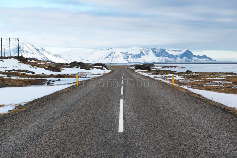 与柏油路和山,冰岛的冬天风景 免版税库存照片