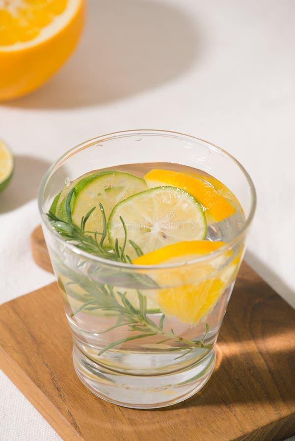 与柑橘、桔子和迷迭香的新鲜的夏天柠檬水 免版税库存照片