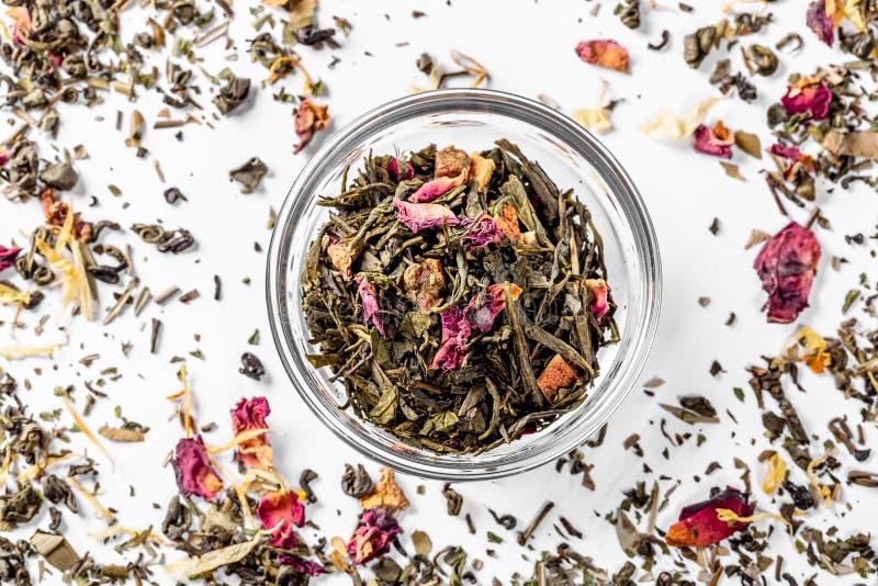 与柑橘干花瓣和片断的绿茶在一个玻璃碗的 焊接的干茶 饮食和健康饮料 flatley 免版税库存图片