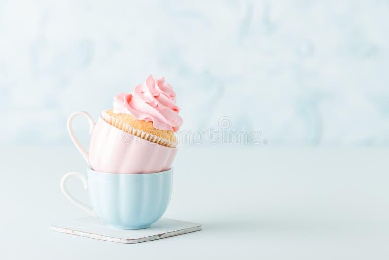 与柔和的桃红色奶油色装饰的杯形蛋糕在蓝色淡色背景的两个杯子中 免版税库存图片