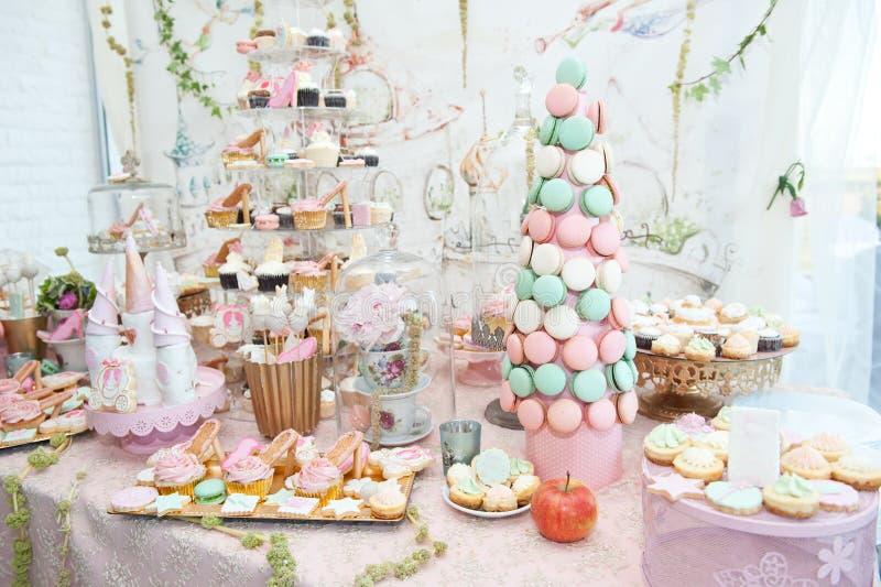与柔和的淡色彩的婚礼装饰上色了杯形蛋糕、蛋白甜饼、松饼和macarons 库存照片