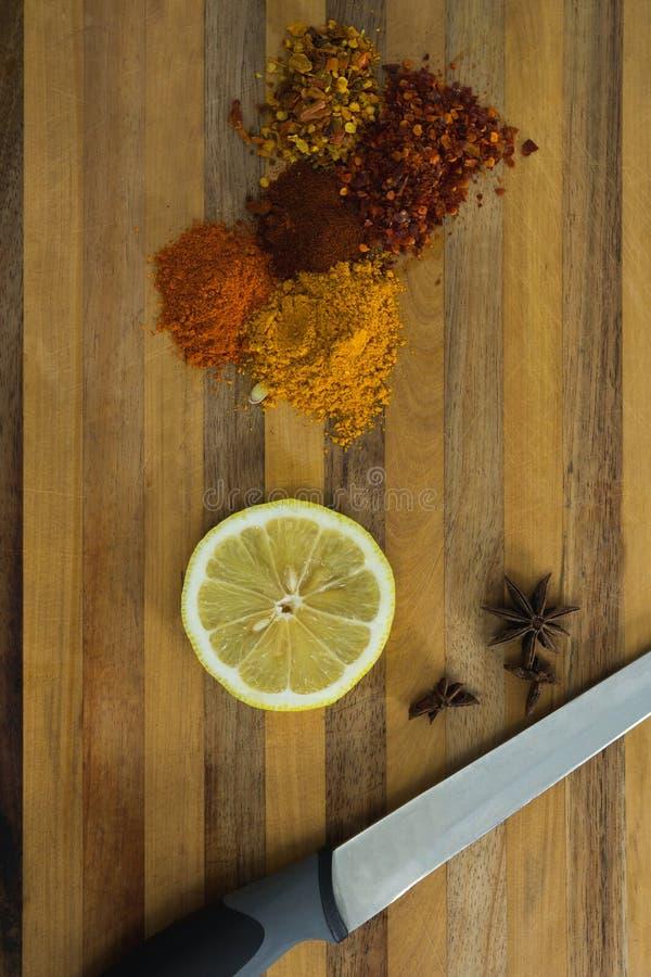 与柠檬切片和刀子的各种各样的香料在砧板 免版税图库摄影