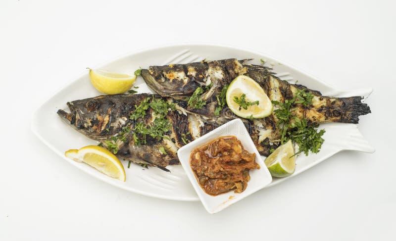 与柠檬切片的烤鱼,烤海鲜在白色隔绝的板材服务 库存照片