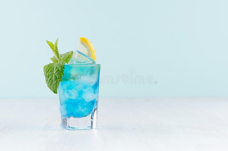 与柠檬切片,冰块,在湿小玻璃的薄菏的夏天新鲜的蓝色库拉索岛鸡尾酒在白色木桌,淡色绿色上 图库摄影