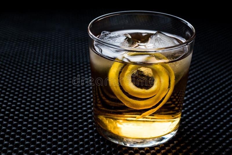 与柠檬皮和冰的Highball鸡尾酒 免版税库存照片
