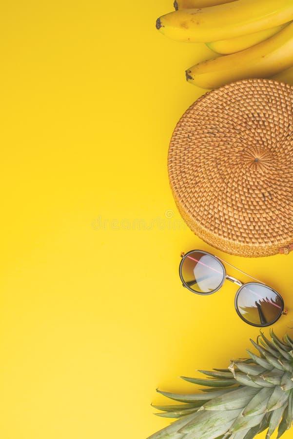 与柳条时尚袋子的夏天五颜六色的背景、妇女的鞋子和热带菠萝、香蕉和太阳镜 夏天时尚 免版税库存照片