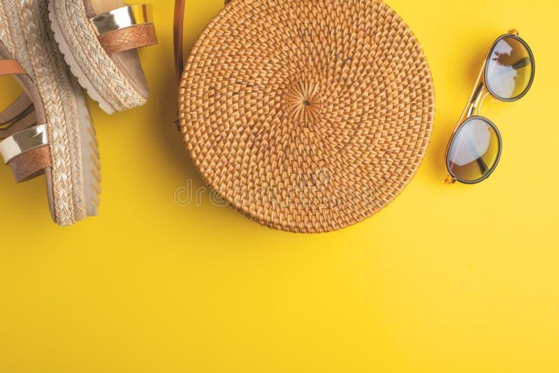 与柳条时尚袋子的夏天五颜六色的背景、妇女的鞋子和热带香蕉和太阳镜 r 库存照片
