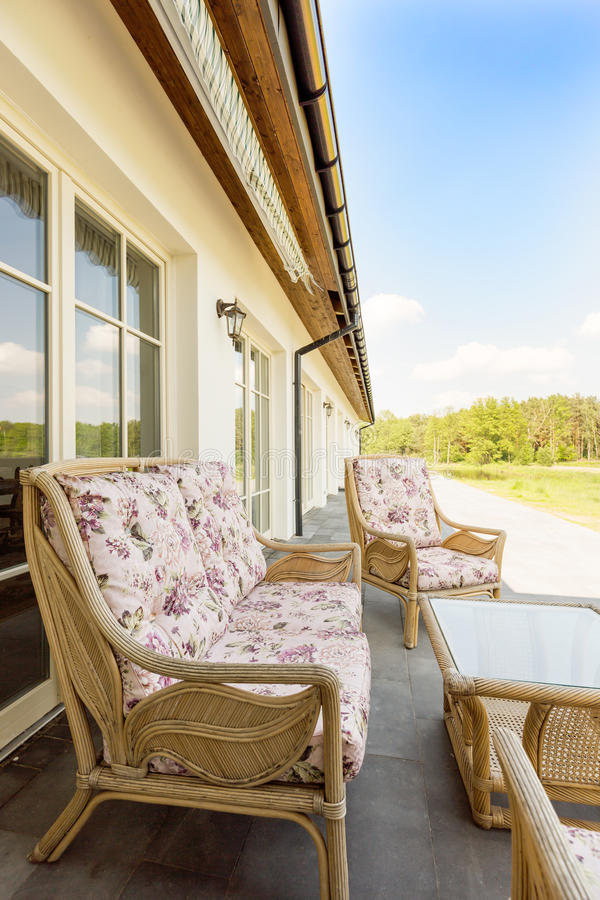 与柳条沙发的长的大阳台 库存图片