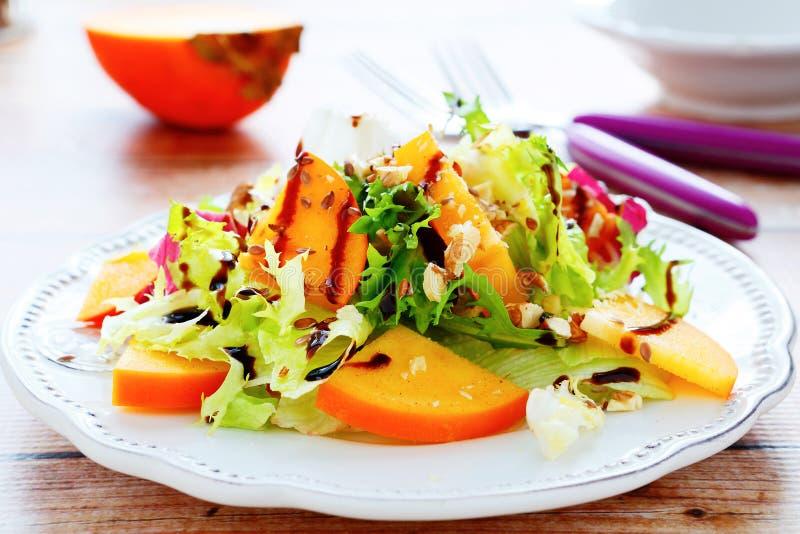 与柿子和坚果的新鲜的沙拉 库存照片