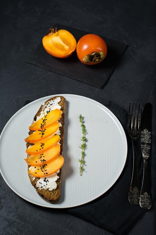 与柿子的三明治和在黑背景的软干酪 免版税库存照片