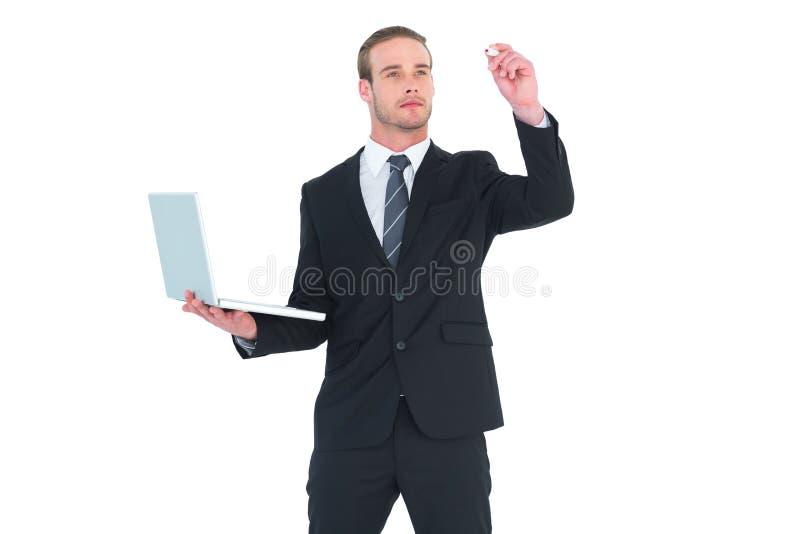 与标志和藏品膝上型计算机的严肃的商人文字 免版税库存照片