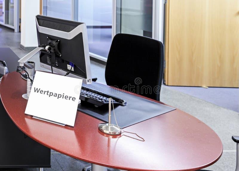 与标志对此写的Wertpapiere的经纪空的办公室站立在书桌上 免版税库存图片