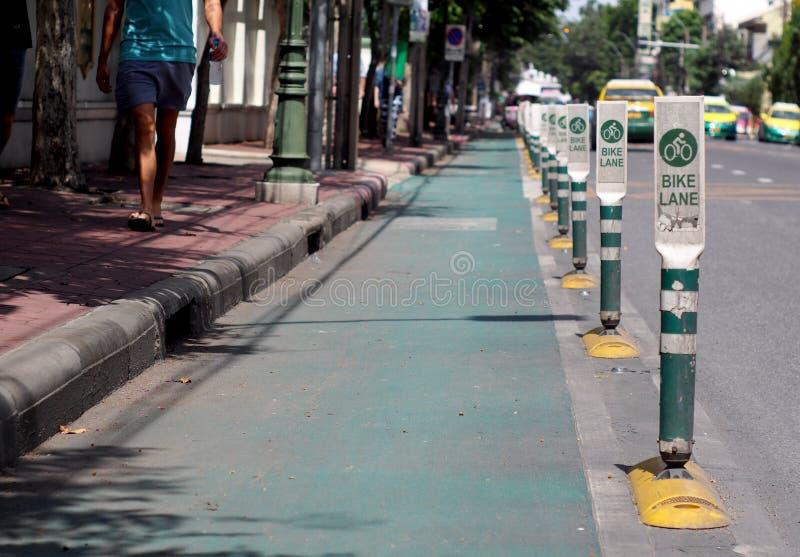 与标志杆列阵的自行车道与在PHRA AHTIT路的路沿昭拍耶河在曼谷 免版税库存图片